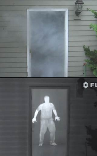 Image showing a smoke filled doorway and a person hiding behind, revealed by a FLIR LS Series thermal imaging camera